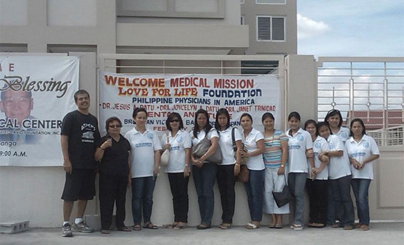 Volunteer Staff standing in in front of the Dr. Jesus A. Datu Medical Center (JADMC)